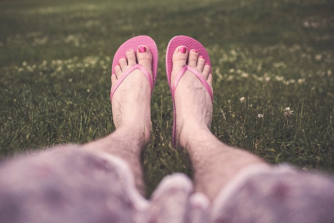 Mannenvoeten in roze slippers: genderneutraal